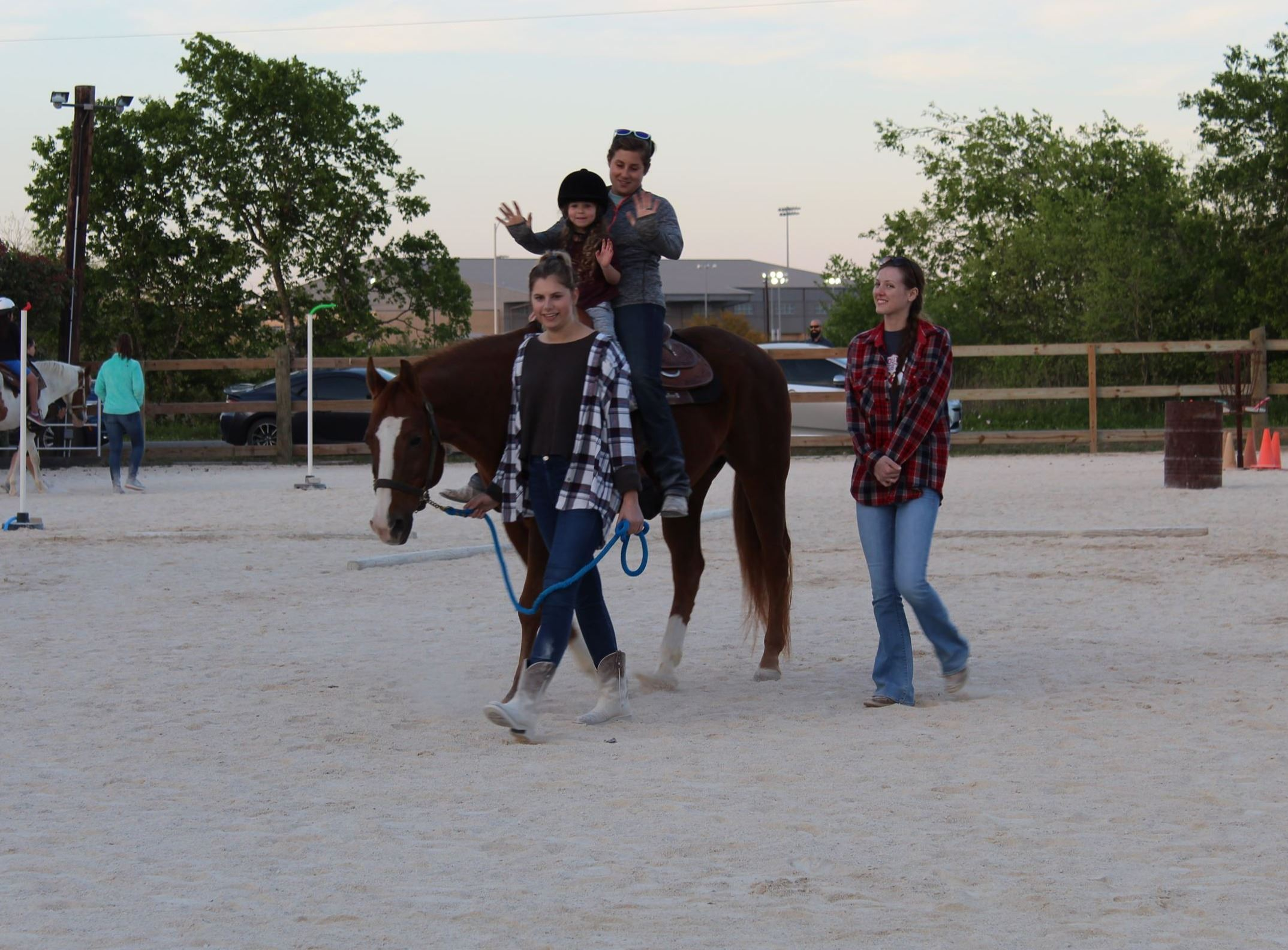 Photo of child on horse with two adults helping the horse to walk slowly in a fenced area