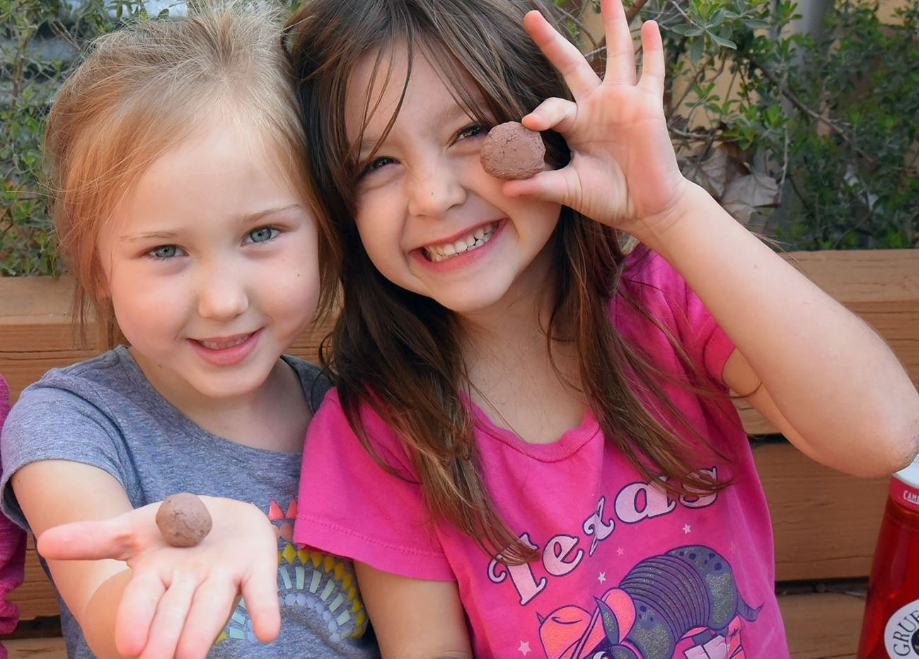 Olivia R. and Dottie A. at the San Marcos Discovery Center holding handmade seed balls. Seed Balls (