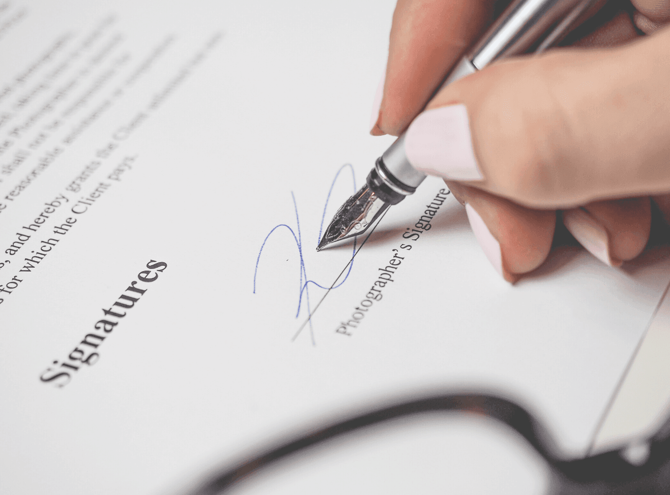 Photo of hand signing a document