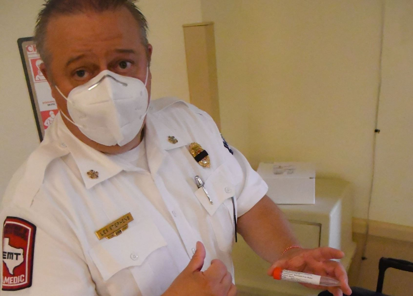 San Marcos Fire Chief Les Stephens holding a test tube with a label.