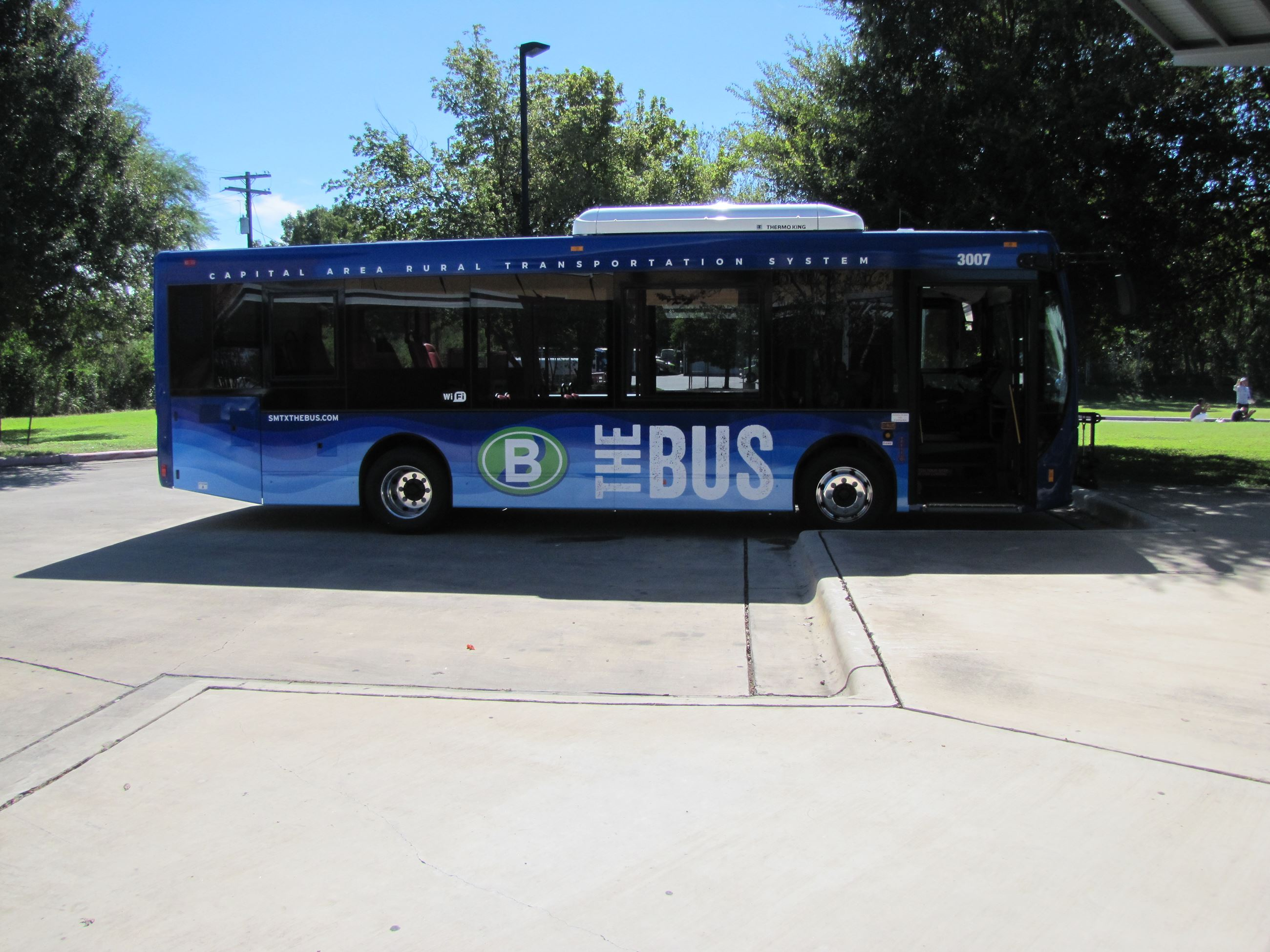 A blue city bus is parked in a parking lot.