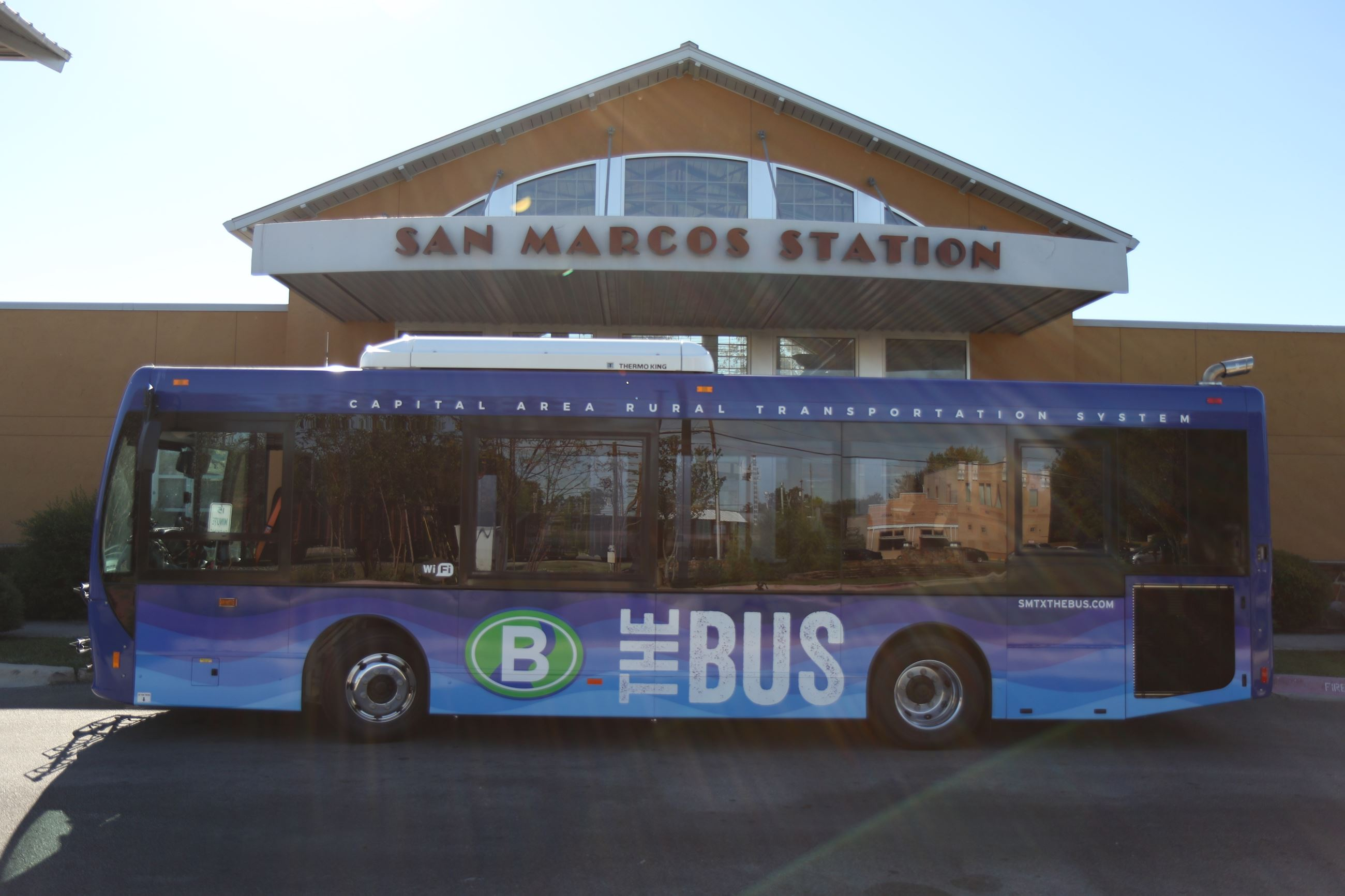 "San Marcos ""The Bus"" vehicle in front of bus station"